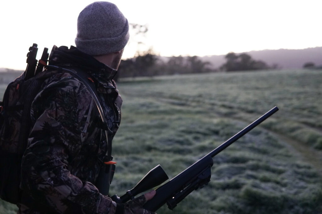 Vortex Ranger 1500 man wearing grey and black camouflage jacket holding rifle walking across a field