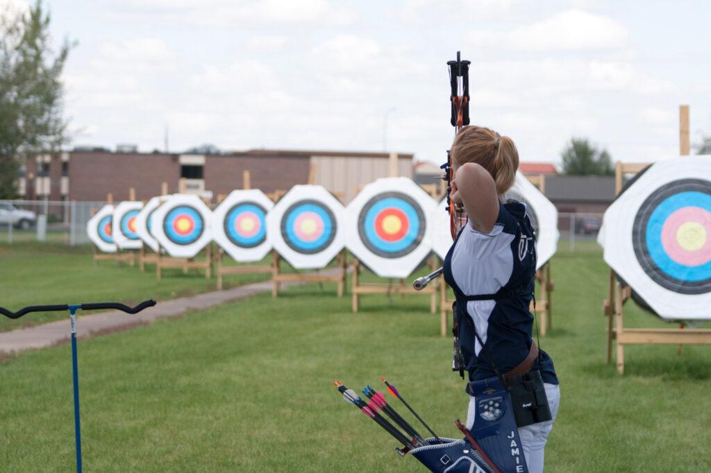 how do laser rangefinders work archery girl in white shirt shooting bow target range